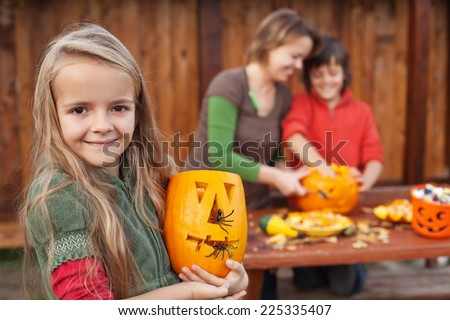 Kids and their mother preparing for Halloween - carving jack-o-lanterns