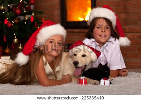 Kids and their pets at Christmas time - laying together at the cozy fire - stock photo