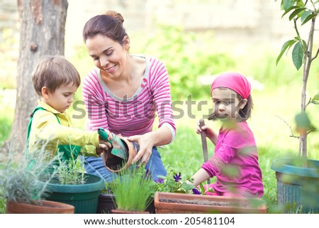 Kids are helping their mother in the garden - stock photo