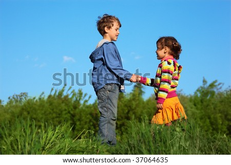 kids at green meadow holding hands - stock photo