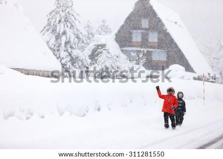 Kids at historic Japanese village Shirakawa-go at winter, travel landmark of Japan - stock photo