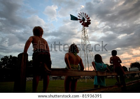 Kids at sunset looking at an old windmill. - stock photo