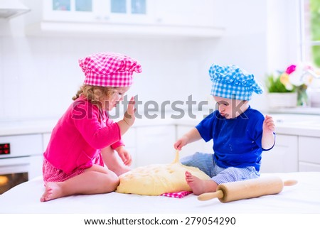 Kids baking. Two children cooking. Little girl and baby boy cook and bake in a white kitchen with modern oven. Brother and sister in chef hats making a pie for dinner. - stock photo