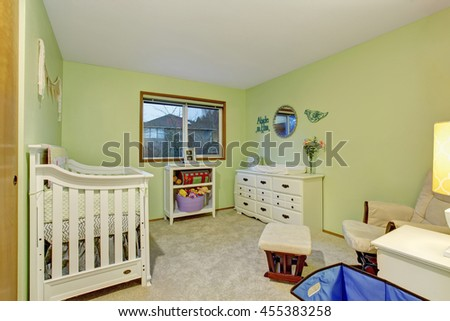 Kids bedroom with white furniture and green painted walls. Also carpet floor