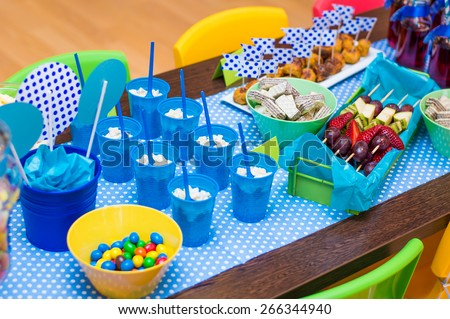 Kids birthday party table with a lot of appetizers, sweets, canape, snacks - stock photo