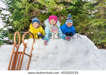 Kids boys and girl behind snow wall with snowballs - stock photo