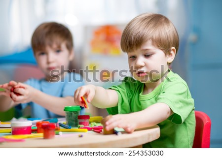 kids boys with play clay toys at home - stock photo