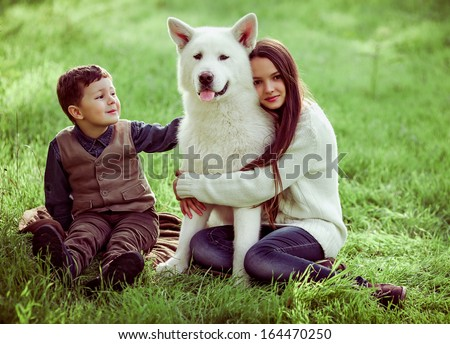 kids, brother and older sister plaing with their dog in the park, autumn  - stock photo