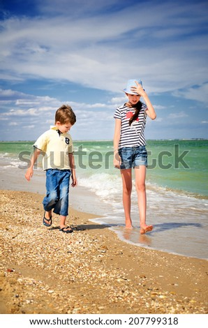 Kids brother and sister walk along the coast. vertical - stock photo