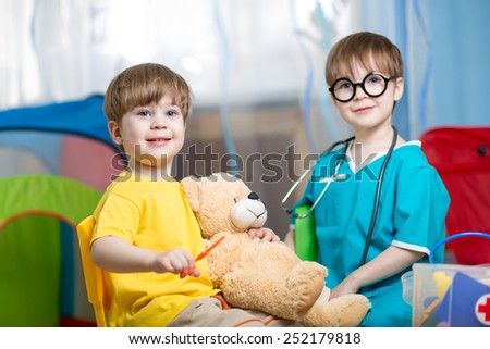 kids brothers play doctor with plush toy at home - stock photo