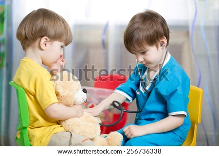 kids brothers playing doctor with plush toy - stock photo