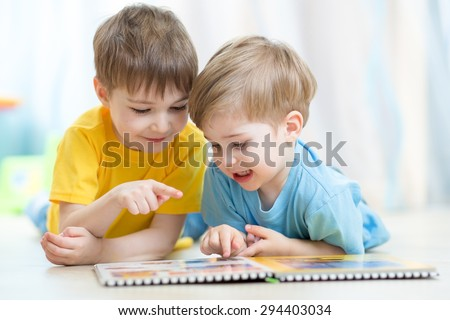 Kids brothers practice reading together looking at book laying on the floor - stock photo