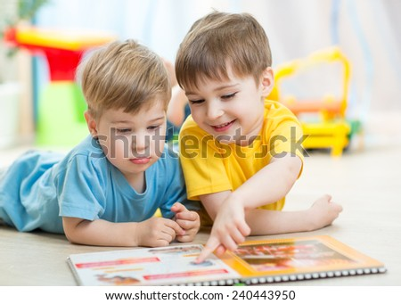 kids brothers read a book at home or nursery - stock photo