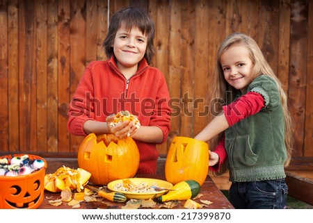 Kids carving their pumpkin jack-o-lanterns - removing the seeds - stock photo