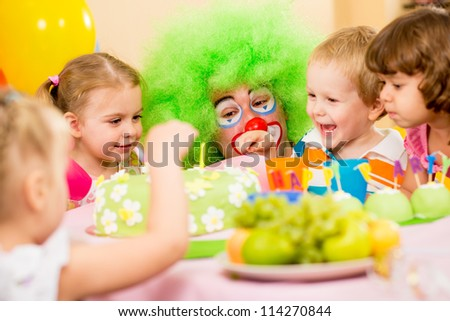 kids celebrating birthday party with clown - stock photo