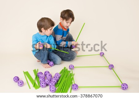 Kids, children building a fort and sharing construction pieces - stock photo