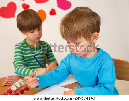Kids, children, doing Valentine's day arts and crafts with hearts, pencils, paper - stock photo