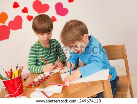 Kids, children, doing Valentine's day arts and crafts with hearts, pencils, paper, love concept - stock photo
