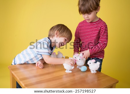 Kids, children having fun and playing with wound up easter bunny toys