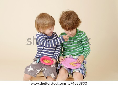 Kids, children sharing a snack, food, suitable for nutrition, eating, sharing, fashion concepts - stock photo