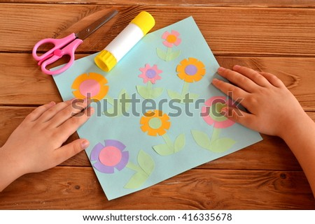 Kids crafts - applique with paper flowers. Child put his hands on a desk. Child made crafts. Scissors, glue - stock photo