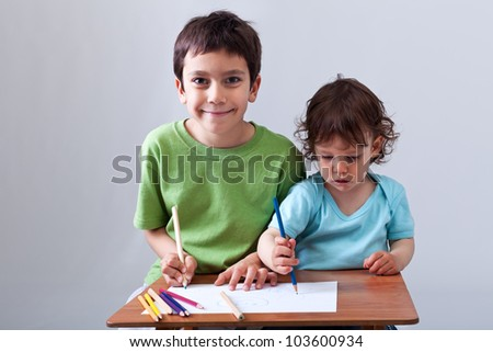 Kids drawing together - preschool boy helping his toddler brother - stock photo