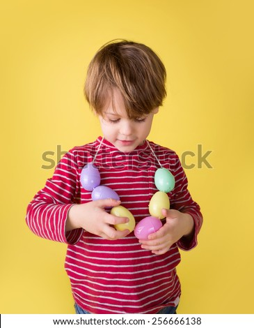 Kids easter activity and crafts: making an easter egg necklace  - stock photo