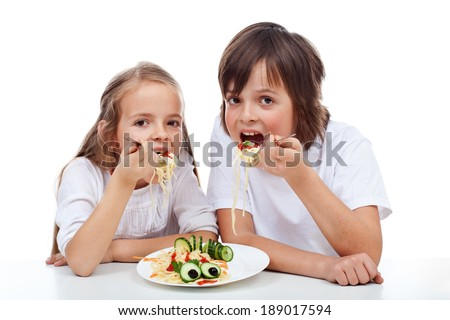 Kids eating a spaghetti dish with big appetite - isolated - stock photo