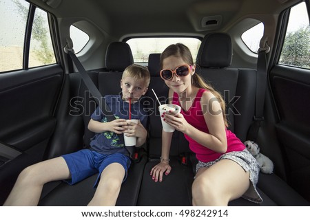 Kids eating a treat in the back of their car after going to a drive thru restaurant