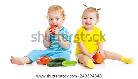 Kids eating fruits and vegetables isolated - stock photo