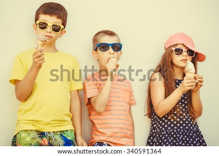 Kids eating gelato and soft serve ice cream. Boys and little girl in sunglasses enjoying summer holidays vacation. Instagram filter. - stock photo