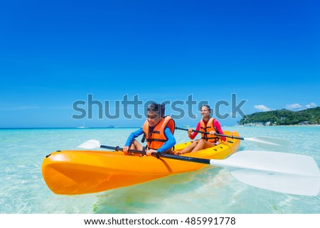 Kids enjoying paddling in orange kayak at tropical ocean water during summer vacation