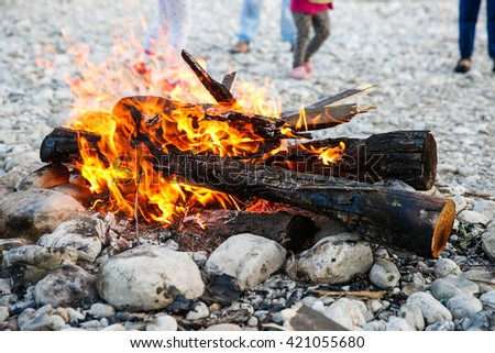 Kids enjoying time by the river and self-made campfire during adventurous camping trip, spending quality time together.  Active natural lifestyle, family time concept.  - stock photo