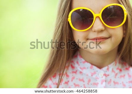 Kids fashion and accessory concept. Portrait of smiling cute little girl in trendy eyewear. Windy summer day. Close up. Copy-space. Outdoor shot