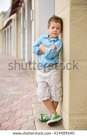 Kids fashion concept. casual child stands with his back against street wall.Outdoor portrait of a cute little blond boy wearing shorts and shirt standing next to stone wall - stock photo