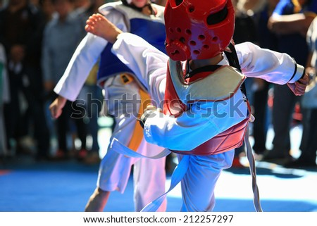 Kids fighting on stage during Taekwondo tournament