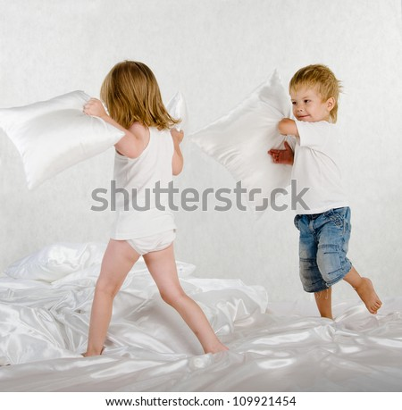 kids fighting pillows in the bedroom - stock photo