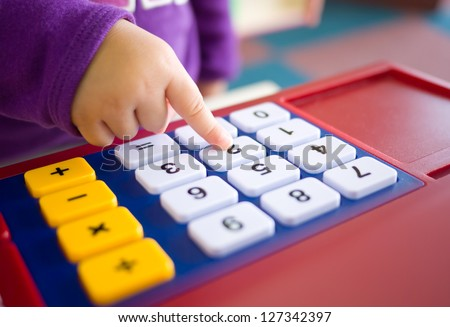 kids finger pressing toy calculator. abstract of fun learning and mathematical thinking.