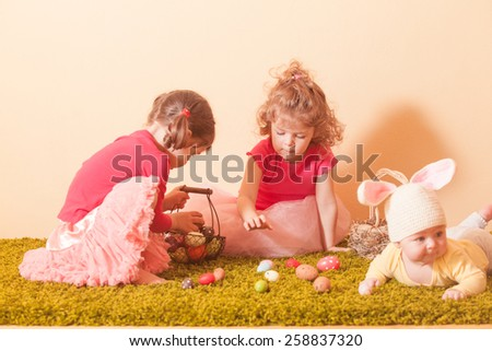 Kids gather colorful eggs to the baskets on Easter Egg hunt - stock photo