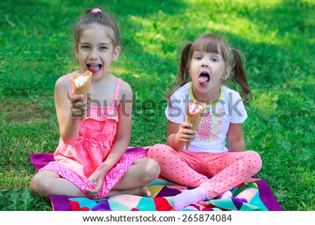 Kids girls friends children eating ice cream and teasing showing off tongues - stock photo
