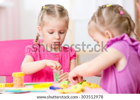 kids girls playing with colorful clay at home