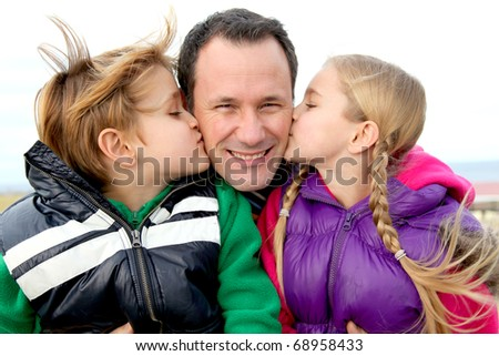 Kids giving a kiss to their daddy - stock photo