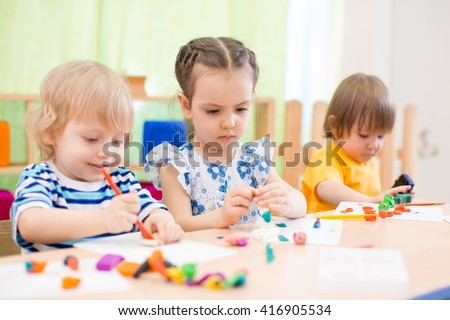 kids group doing arts and crafts in day care centre - stock photo