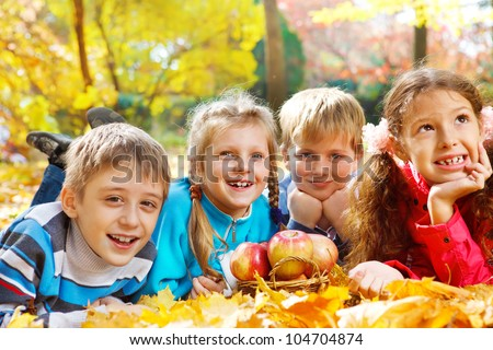 Kids group lying in autumn park - stock photo
