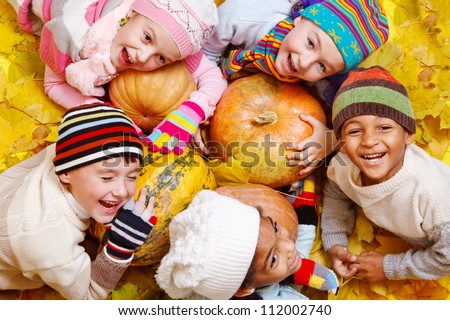 Kids group on yellow leaves and pumpkins - stock photo