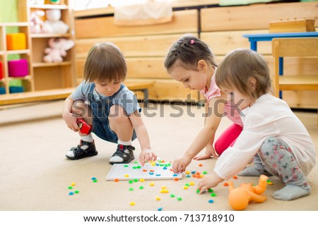 kids group playing mosaic game in kindergarten or daycare center