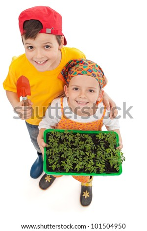 Kids growing food - holding spring seedlings and gardening tools, isolated - stock photo