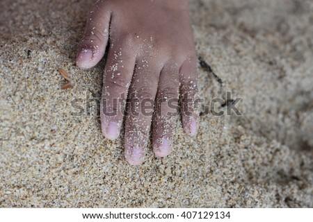 kids hand on sand - stock photo