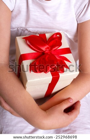 Kids hands holding a gift box with red satin bow close-up. Mother's day, father's day concept. - stock photo
