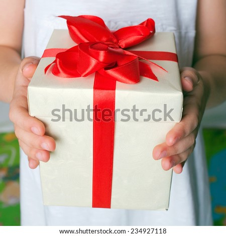 Kids hands holding a gift close-up. Mother's day, father's day concept. - stock photo